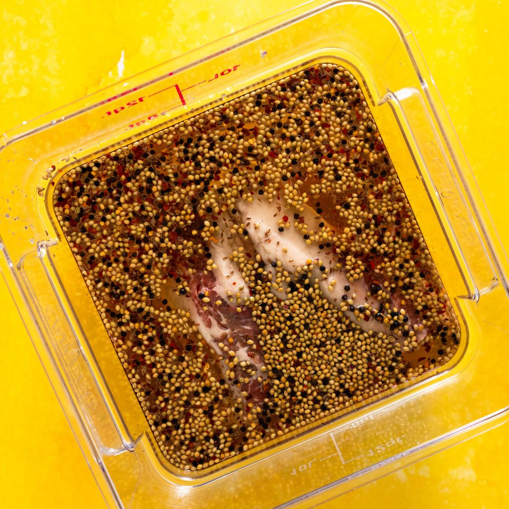 Brisket in brine in Cambro container on yellow surface