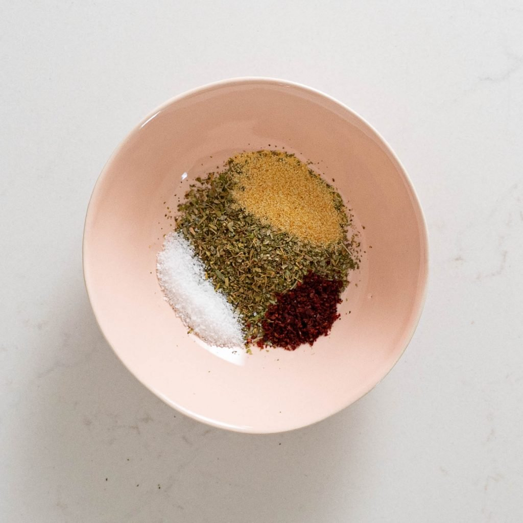 Pink bowl with salt, Italian seasoning, garlic powder, and sumac