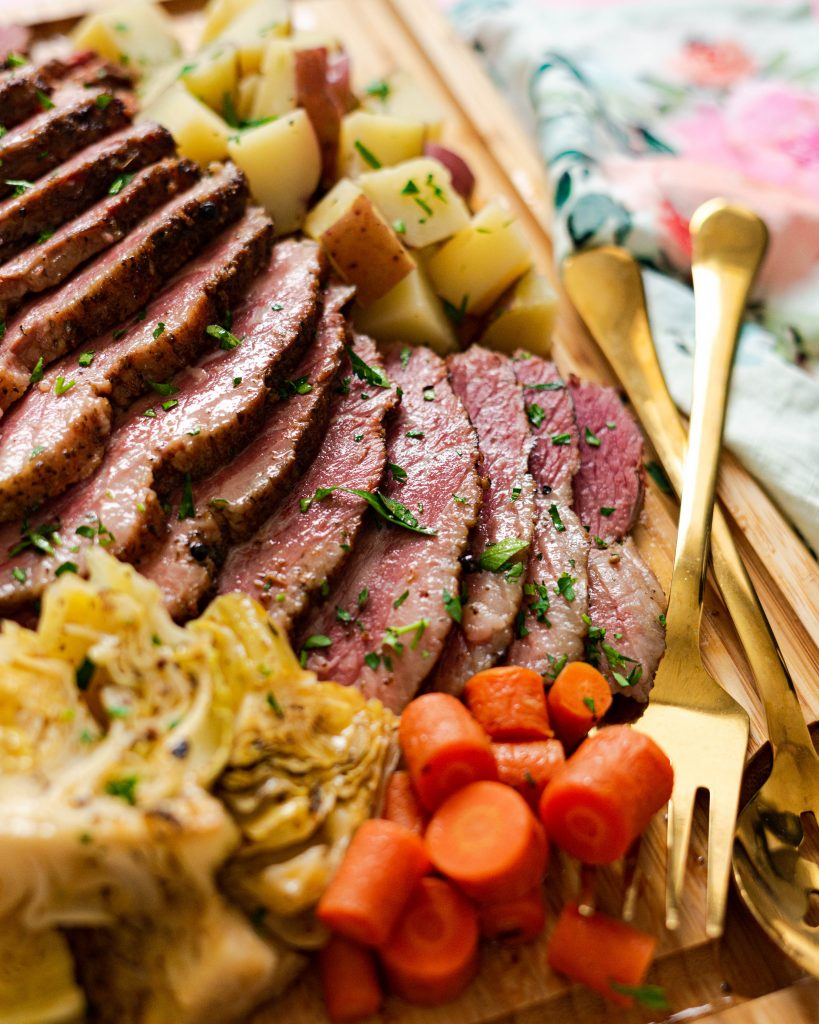 Corned beef, carrots, cabbage, potatoes on wood cutting board