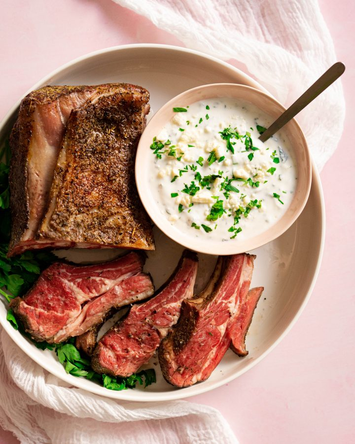 White platter with sliced rack of lamb and bowl of feta sauce on pink surface