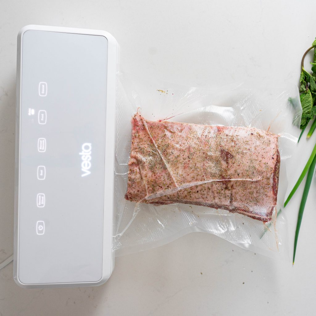 Vacuum sealing rack of lamb on white surface