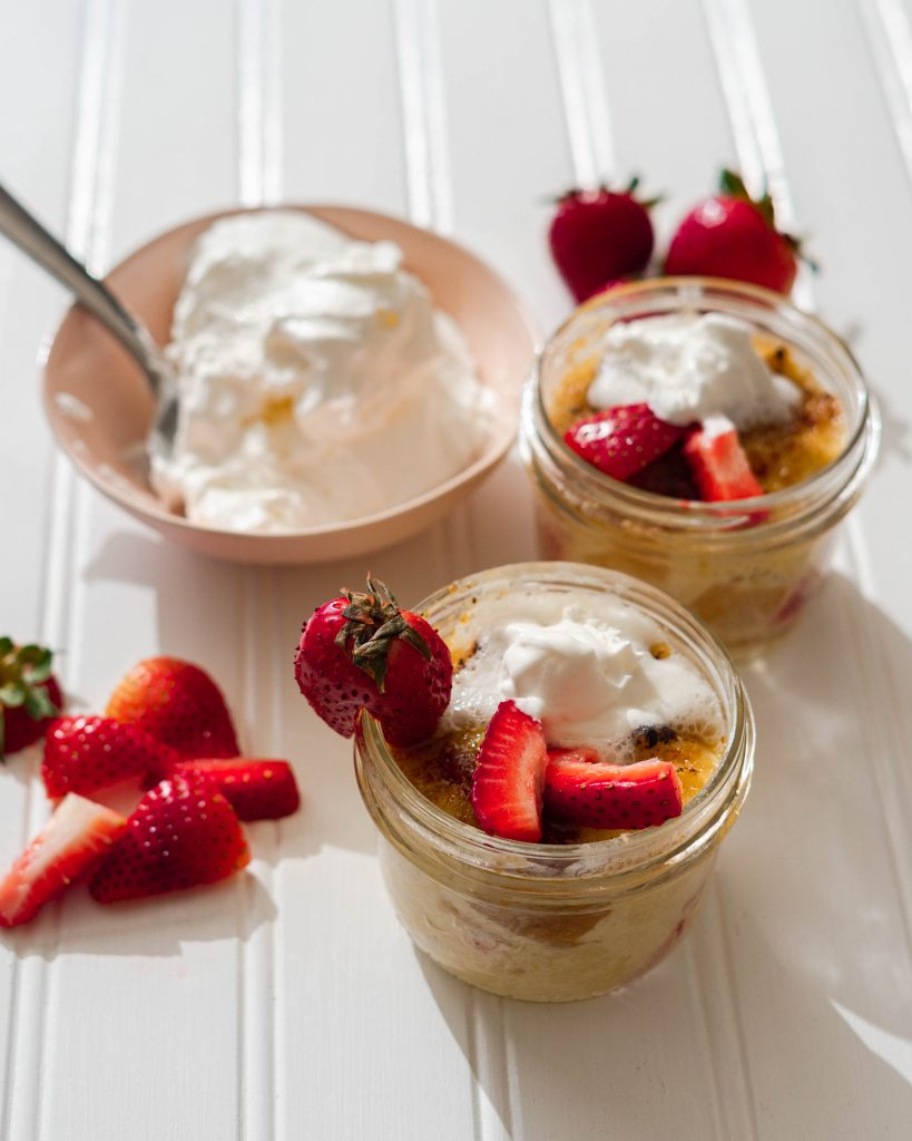 Sous vide bread pudding in glass jars topped with whipped cream