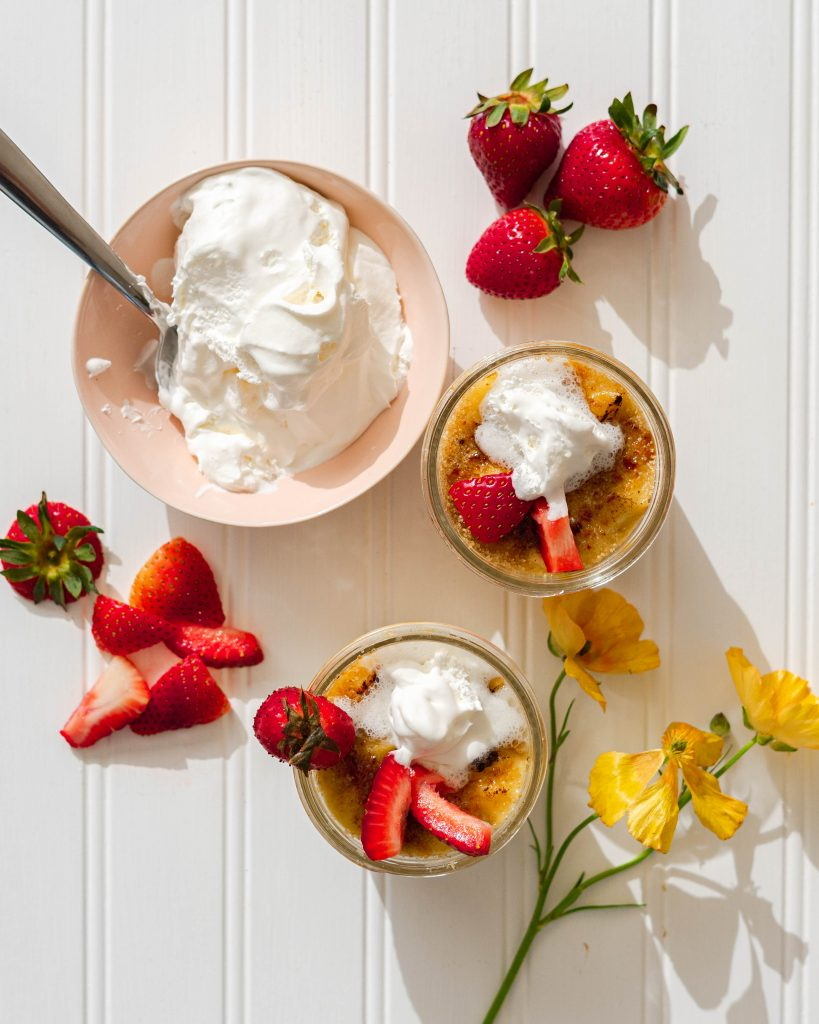 Jars of strawberry meyer lemon sous vide bread pudding and bowl of whipped cream on white surface