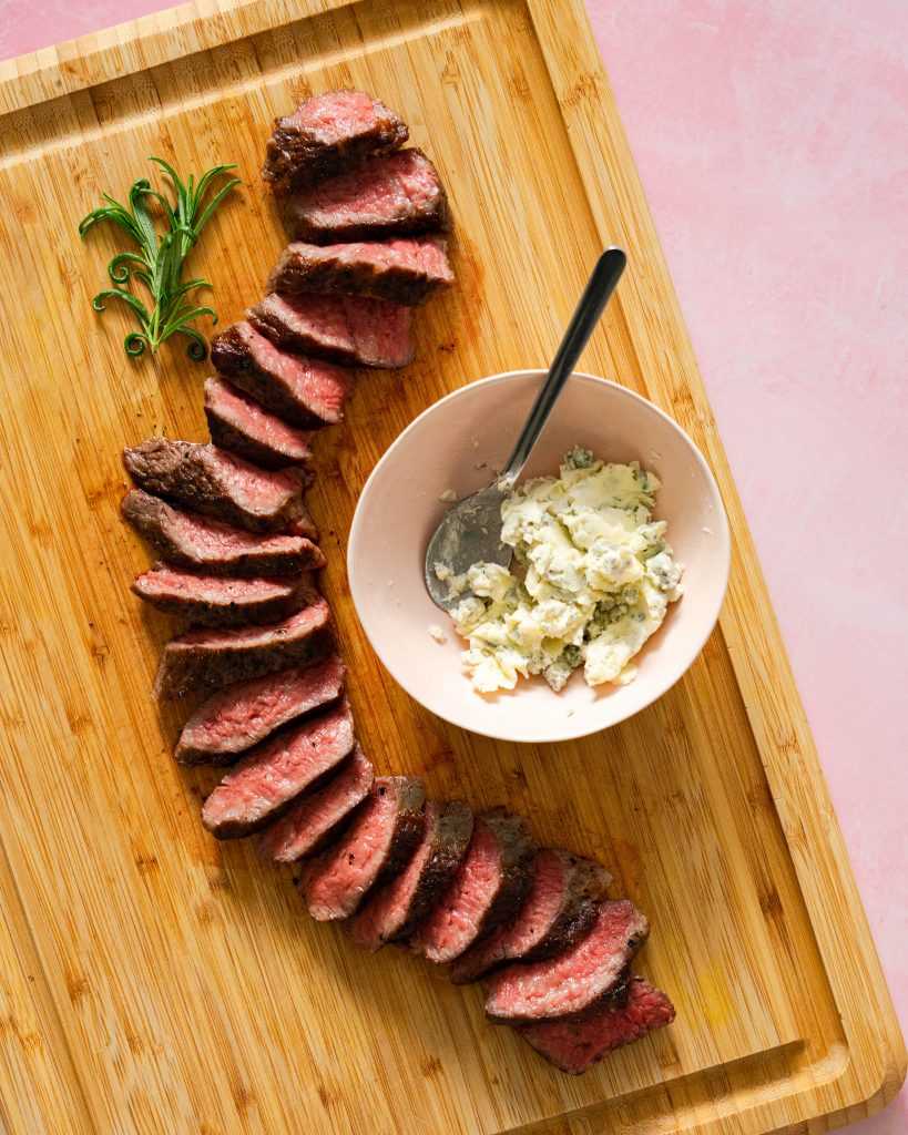 Sliced tri-tip and bowl of blue cheese butter on wood cutting board on pink surface