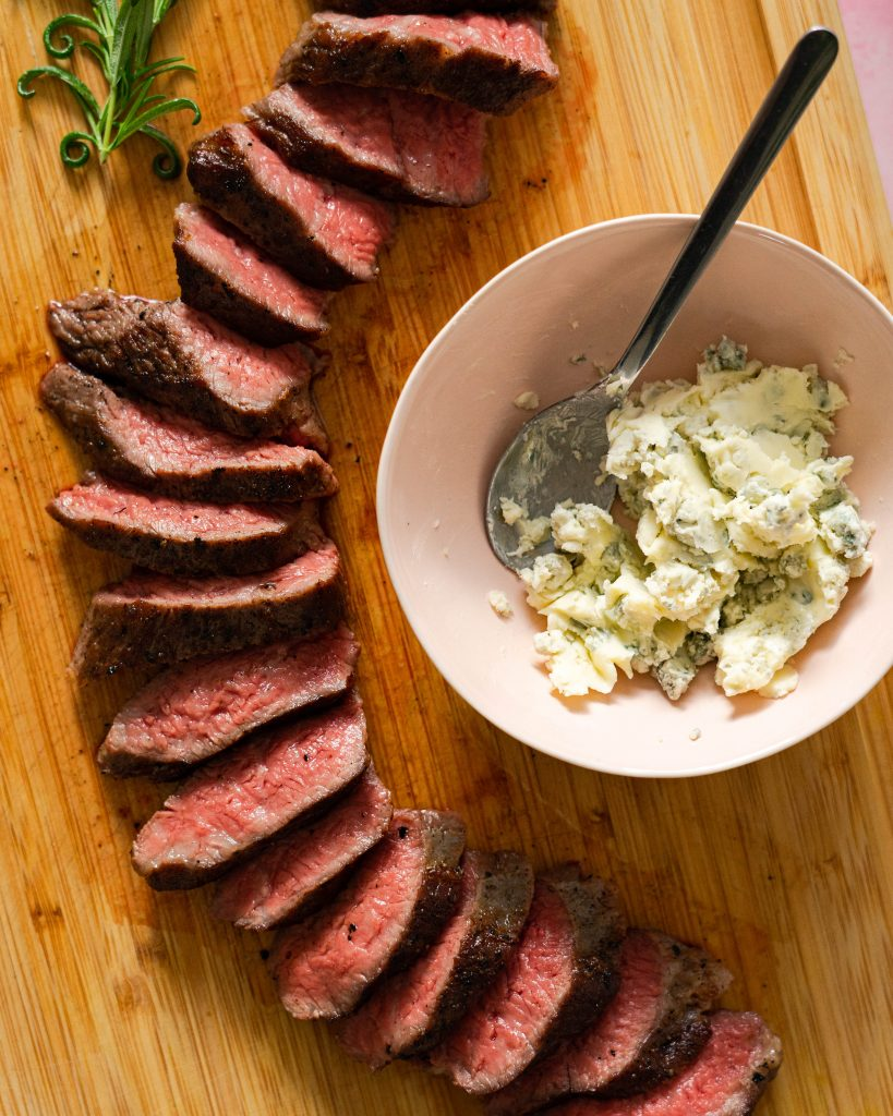Sliced tri-tip steak and pink bowl with blue cheese butter on wood cutting board