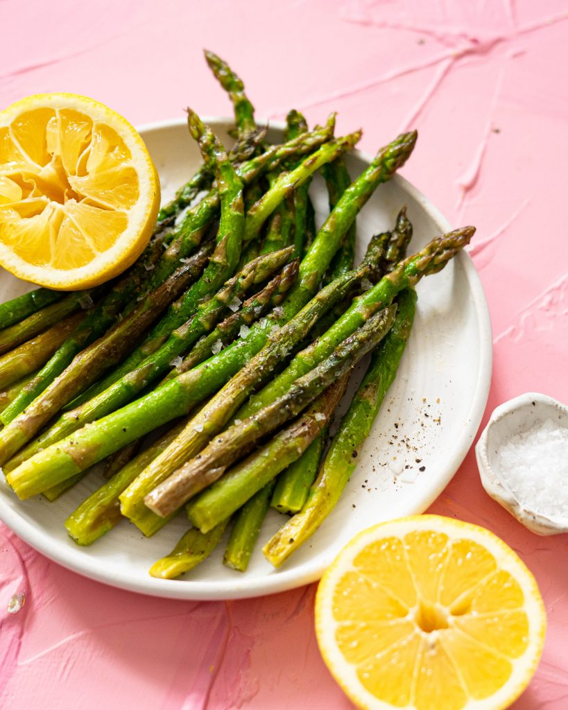 Asparagus spears on a white plate with lemons on a pink surface