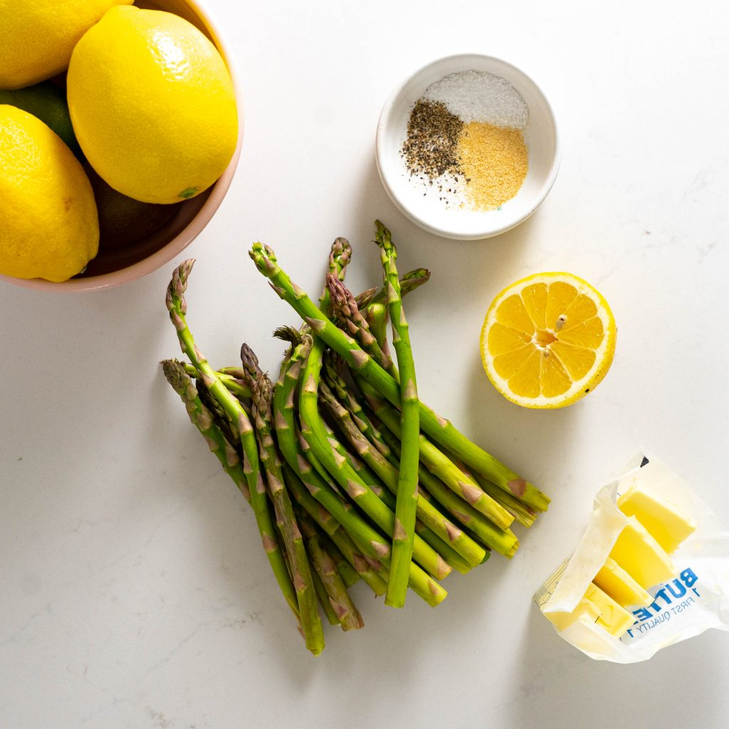 Bowl of lemons, stalks of asparagus, seasoning, sliced lemons, and butter on white surface.