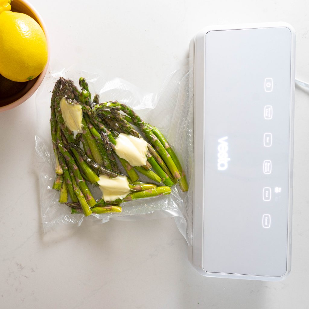 Asparagus being vacuum sealed on white surface