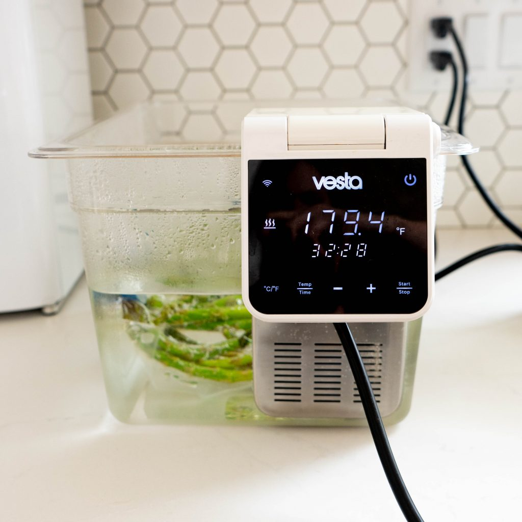 Asparagus in sous vide water bath on white surface