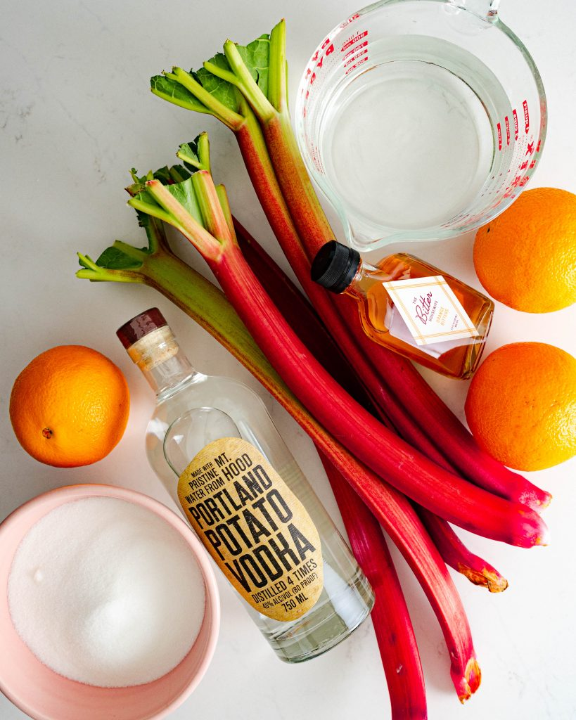 Homemade aperol ingredients on white surface