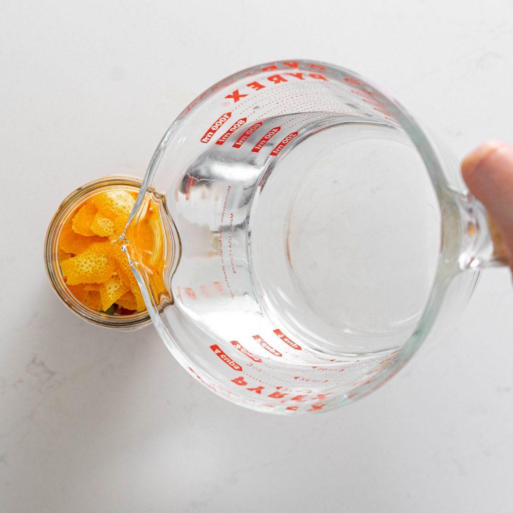 Pouring vodka over fruit in jar