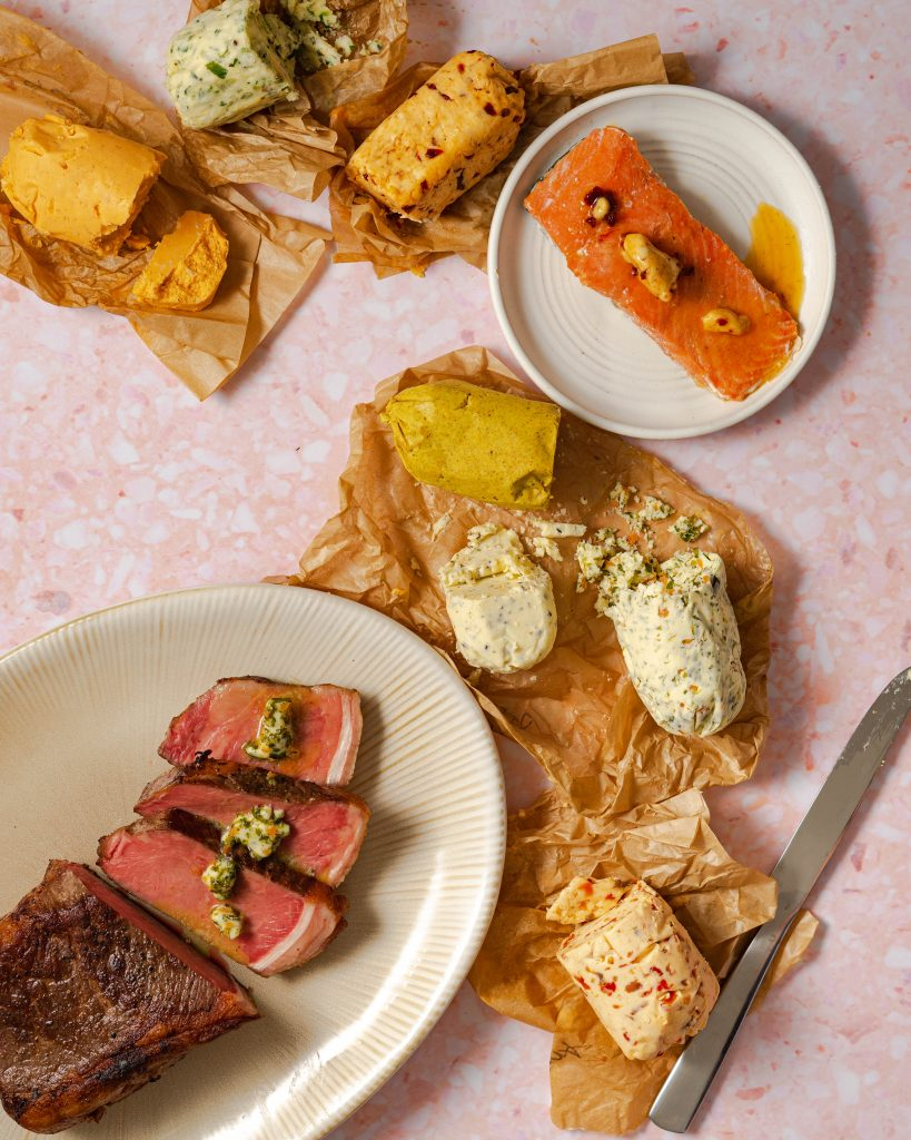 Compound butters on parchment paper, steak on platter, salmon on plate on pink surface