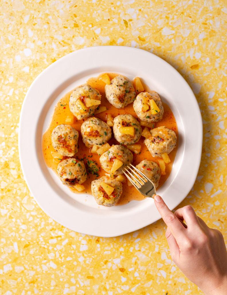 Meatballs in a firecracker pineapple sauce on white platter