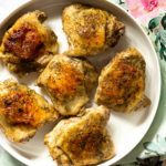 Cooked chicken thighs on white platter on floral napkin