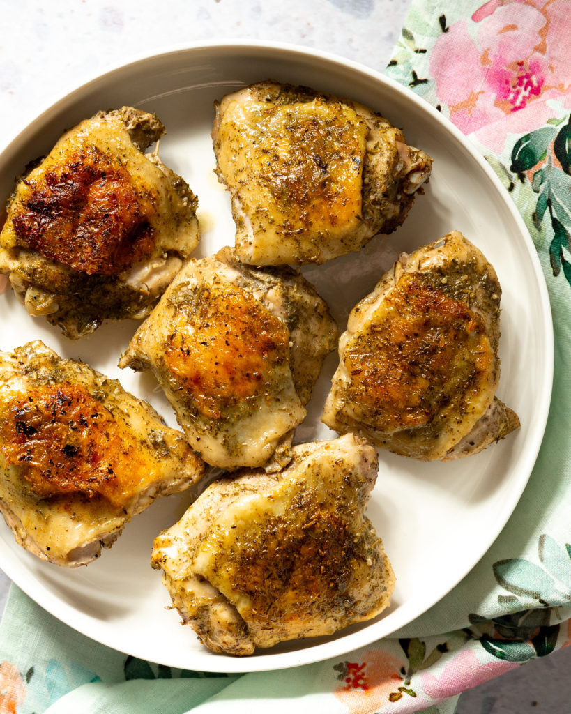 Cooked chicken thighs on white platter with floral napkin underneath