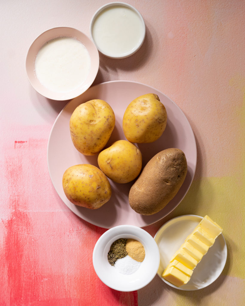 Mashed potato ingredients on pink and yellow surface.