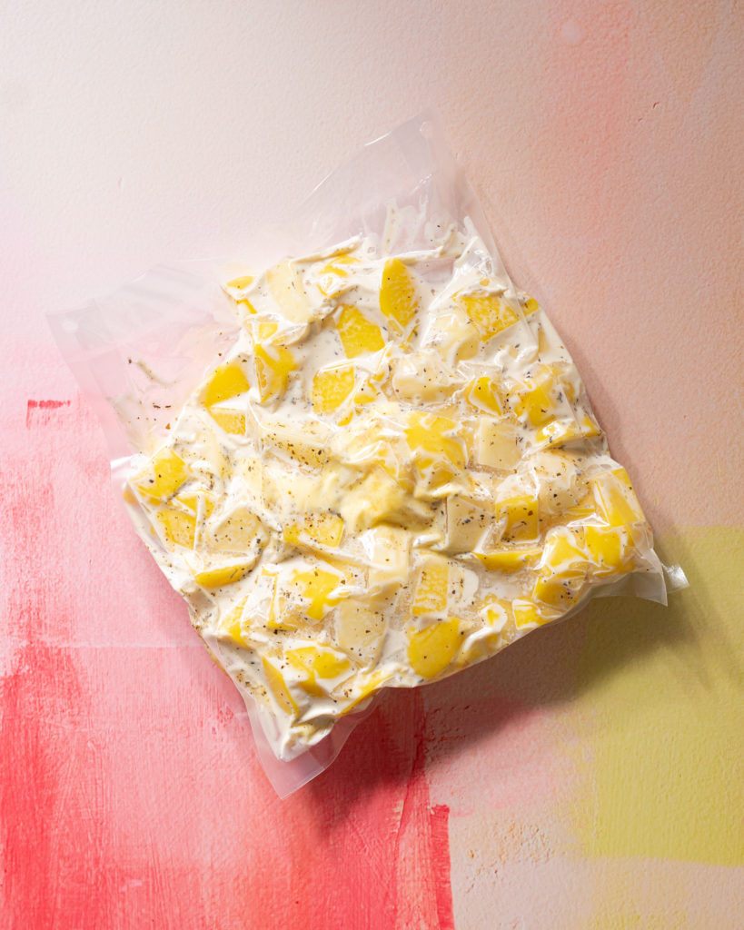 Mashed potato ingredients in vacuum seal bag on pink and yellow surface.