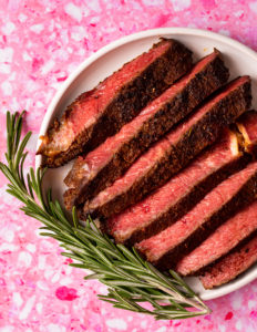 Sliced steak cooked from frozen on a white plate on pink background